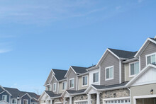 Homes With Gable Roofs And Gray Exterior Walls Against Blue Sky In The Suburbs