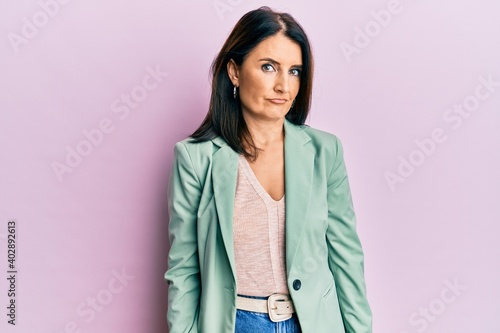 Fototapeta Middle age brunette woman wearing casual clothes skeptic and nervous, frowning upset because of problem