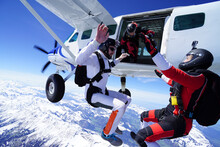 Skydivers Jump Out Of Plane And Perform Tricks Above Snowcapped Mountains