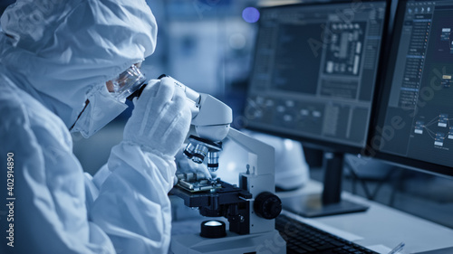 Research Factory Cleanroom: Engineer / Scientist wearing Coverall and Uses Microscope to Inspect Samples, Developing High Tech Modern Technology for Medical and High Precision Electronics Industry