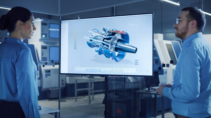 Fototapeta Tenis Office Meeting: Confident Female Engineer Talks to Project Manager, Watching Interactive Digital Whiteboard TV that Shows New Sustainable Eco-Friendly Engine 3D Concept. Modern Factory with Machinery