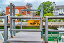 Private Property Keep Out Sign Against Wooden Dock On Canal In Long Beach CA