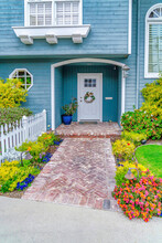 Facade Of Home With Blue Wall White Door And Beautiful Landscaped Garden