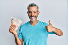 Middle Age Grey-haired Man Holding United Kingdom Pounds Smiling Happy And Positive, Thumb Up Doing Excellent And Approval Sign