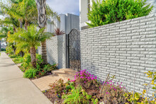 Pathway Along Wrought Iron Gate And Brick Fence At The Entrance Of Modern Home