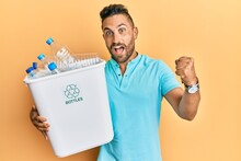 Handsome Man With Beard Holding Recycling Wastebasket With Plastic Bottles Screaming Proud, Celebrating Victory And Success Very Excited With Raised Arms
