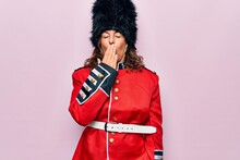 Middle Age Beautiful Wales Guard Woman Wearing Traditional Uniform Over Pink Background Bored Yawning Tired Covering Mouth With Hand. Restless And Sleepiness.