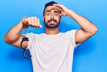 Young Hispanic Man Holding Prisoner Handcuffs Stressed And Frustrated With Hand On Head, Surprised And Angry Face