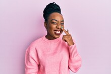 Young African American Woman Wearing Casual Winter Sweater Pointing With Hand Finger To Face And Nose, Smiling Cheerful. Beauty Concept