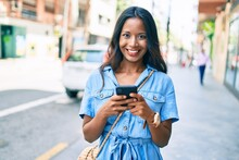 Young Beautiful Indian Woman Smiling Happy Using Smartphone Walking At The City