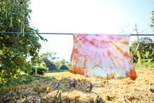 Natural Color Dyeing T-shirt Hanging On The Rope Over Nature Background, Tie Dye With Natural Dye