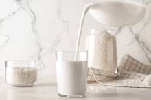 Pouring Of Rice Milk From Jug Into Glass On Table