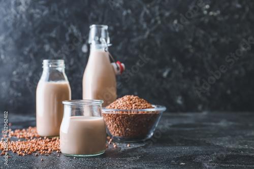 Obraz Glassware with tasty buckwheat milk and grains on table - fototapety do salonu