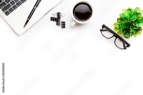 Fototapeta Flat lay, top view office table desk. Workspace with, laptop,office supplies, pencil, green leaf, and coffee cup on white background. obraz na płótnie