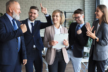 Happy Modern Business People Are Keeping Arms Raised And Expressing Joyful While Standing In Office.