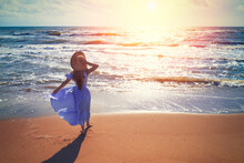 Seascape On A Sunny Summer Day. Woman On The Beach. Young Happy Woman Walking Carefree On The Sea In Long Blue Fluttering Dress And Straw Sun Hat