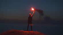 The Man Holding A Fire Stick On The Mountain Top Near The Sea