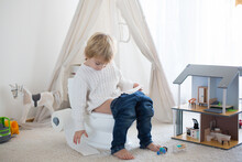 Cute Toddler Child, Boy, Sitting On A Baby Toilet Potty, Playing