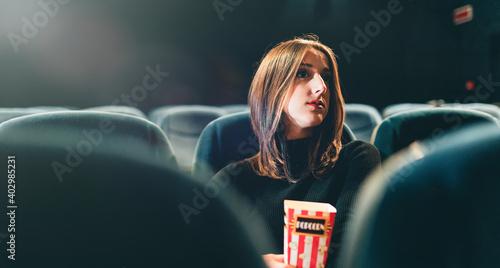 Fototapeta Bella ragazza seduta al cinema con pop corn si guarda un film