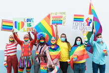 Multiracial Gay People With Rainbow Mask At Lgbt Pride Parade Outdoors - Focus On Faces