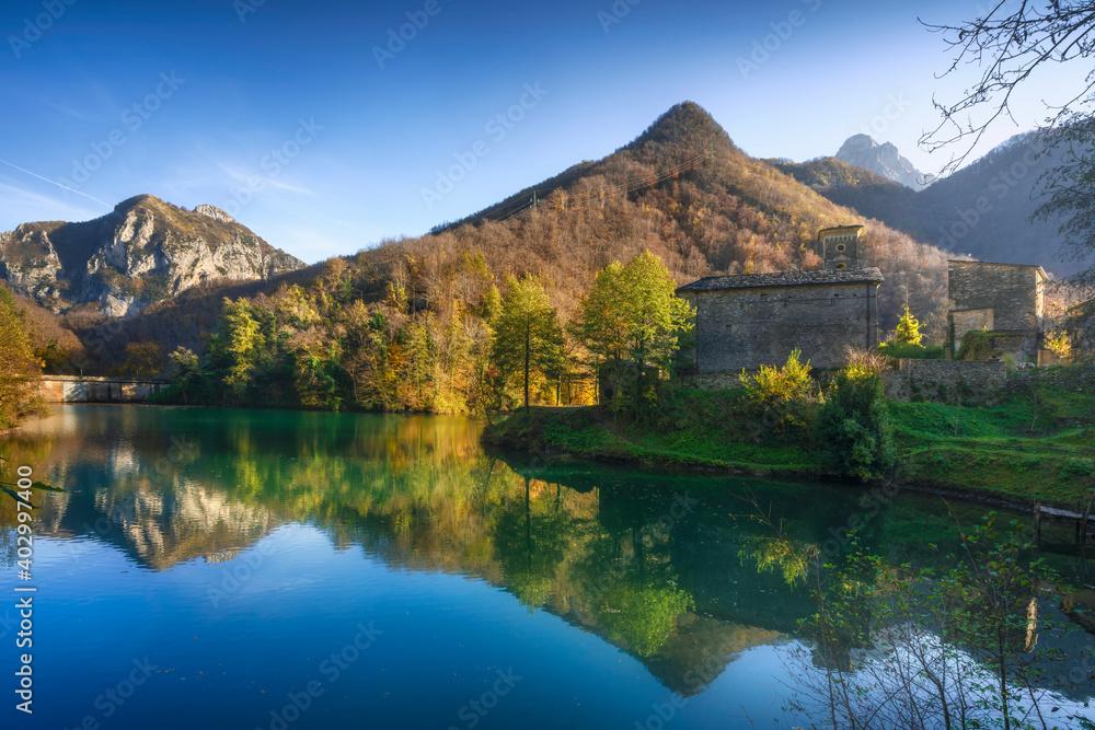 Isola Santa medieval village and lake in autumn foliage. Garfagnana, Tuscany, Italy.