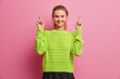 Leinwandbild Motiv Studio shot of pretty European girl makes desirable wish crosses fingers believes in good luck waits for excellent news smiles pleasantly wears loose knitted jumper isolated over pink background.