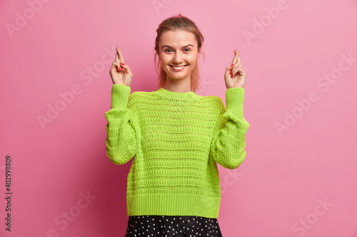 Studio shot of pretty European girl makes desirable wish crosses fingers believes in good luck waits for excellent news smiles pleasantly wears loose knitted jumper isolated over pink background.