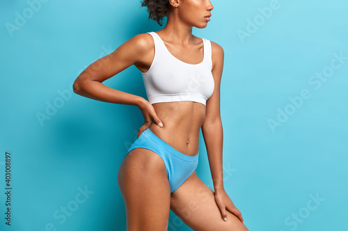 Unrecognizable dark skinned woman in cropped top and panties has slim figure flat belly demonstrates perfect body after loosing weight