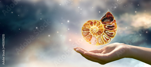 Photographie Human hand holding ammonite fossil in universe against space sky and shining stars background