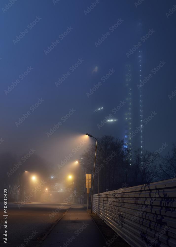 Fototapeta An empty illuminated motorway and closed shops in a fog at night. Road sign close-up. Dark urban scene, cityscape. Riga, Latvia. Dangerous driving, concept image