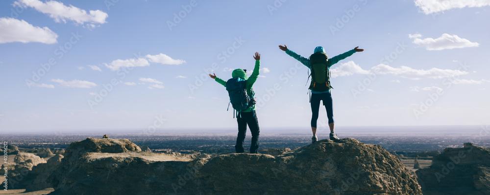 Fototapeta Two women backpackers hiking on sand desert