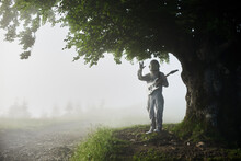 Talented Spaceman Wearing White Space Suit And Helmet Holding White Guitar Is Standing Under A Huge Beautiful Tree In Foggy Summer Morning, Concept Of Exploring Earth