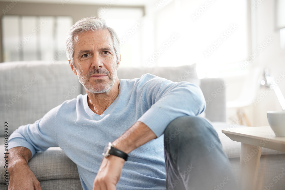 Fototapeta Portrait of attractive senior man with blue sweater relaxing at home