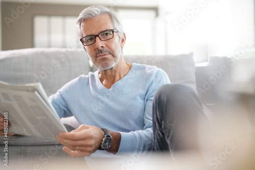 Attractive senior man with eyeglasses relaxing at home reading newspaper