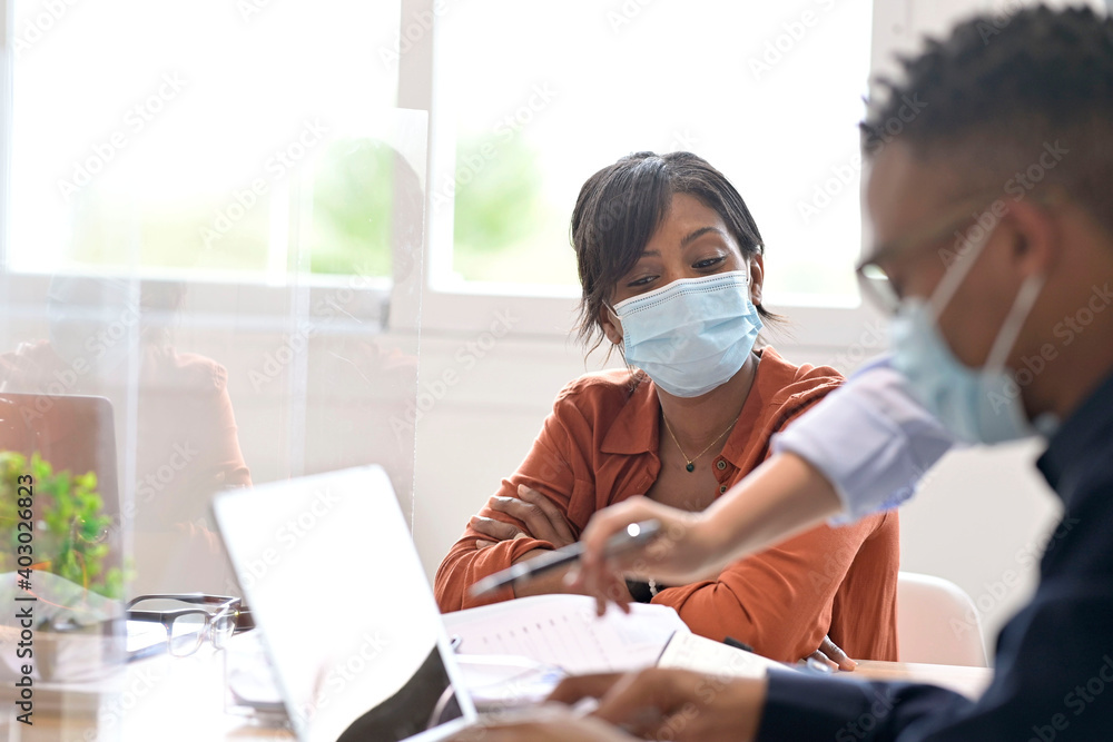 Fototapeta Coworkers in open space office, wearing surgical face mask, 19-ncov pandemic
