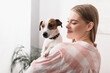young cheerful woman holding in arms jack russell terrier in living room