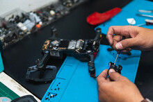 Concentrated Man Repairing Drone Detail With Screwdriver