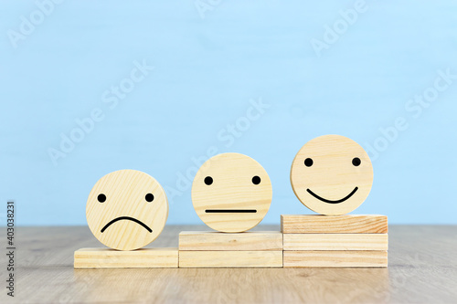 Concept image of satisfaction level. wooden circles with emotions