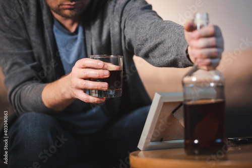 Fotografiet cropped view of drunk man with glass and bottle of whiskey sitting near photo fr