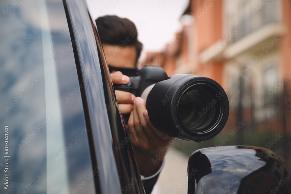 Fototapeta Private detective with camera spying from car, focus on lens