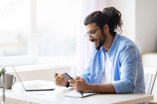 Canvas Print Young arab guy using smartphone and credit card at home, shopping online