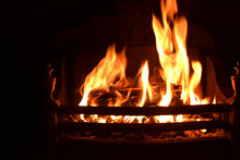 Closeup Of Dancing Flames With Dark Background Of Burning Wooden Logs In Fireplace, Warming Light In Christmas Holidays