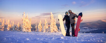 Banner Snowboarders Friends Woman And Man Hug And Hold Snowboards On Background Of Winter Forest And Sunset