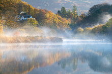 Beautiful Autumn Misty Morning In The Langdale Valley, Lake District, With A Quaint House And Chimney Smoking