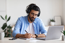 Distance Learning. Young Arab Guy In Headphones Studying With Laptop At Home