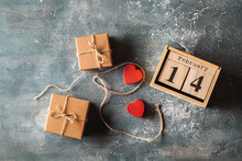 Wooden Calendar Of Blocks With The Date Of February 14, Cardboard Gift Boxes Tied With A Rope And Two Red Hearts On The Grey Concrete Background. Flat Lay. Happy Valentine's Day. Love Expression