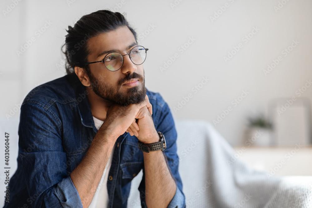 Fototapeta Portrait Of Thoughtful Millennial Arab Guy In Glasses Resting Head On Hands