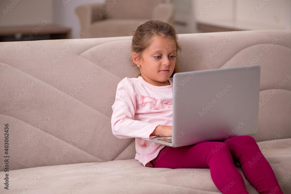 Fototapeta Small girl in tele-education concept at home