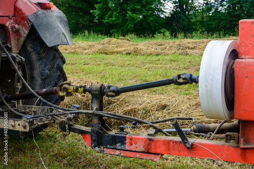 Tractor and cardan shaft for coupling equipment, tractor in the field during haymaking.