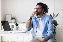 Thoughtful Young Arab Male Freelancer Sitting At Desk At Home, Looking Aside